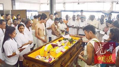 孙子孙女根据印度传统风俗,围绕着棺木颂唱印度圣歌。