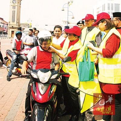 达祖为一名摩托车骑士换上新头盔。