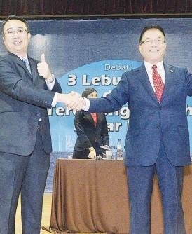 辩论后梁德明(左)与林峰成握手示意。