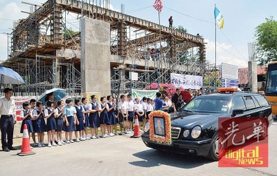 林兴镇校长的灵车在启新小学短暂停留,师生列队做最后敬礼,背景为如火如荼兴建中的启新礼堂。