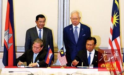 纳吉以及洪森见证代表通讯以及多媒体部的农长拿督斯里阿末沙比里,以及柬埔寨资讯部长乔卡纳里(以者右)签字谅解备忘录。