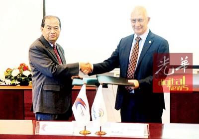 大马渔业局与世界渔业中心签署备忘录,图为依斯迈(左)与世界渔业中心总监乃哲交换已签署的备忘录。