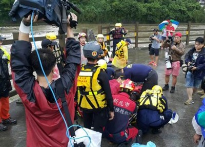 救援人员目前仍在搜救最后一名失踪者,图为周日搜救人员为救出的女子进行急救。