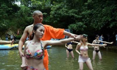 有僧人手把手教导学员姿势。