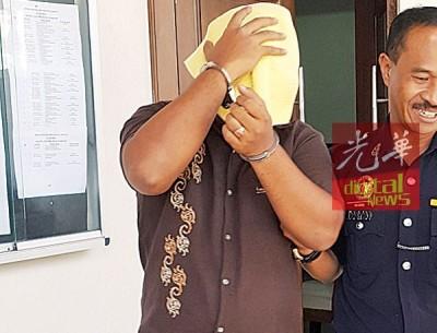 被告莫哈末哈罗门查基被押出法庭时遮盖脸部避开媒体镜头。