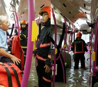 巴士受困水中,雨水也灌入巴士内,须出动民防人员协助疏散司机和乘客。
