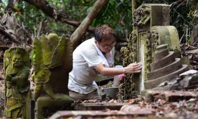 吴安全将面粉涂抹在墓碑的刻痕上,尝试辨别出墓碑上的题词。