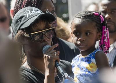 死者女友雷诺兹抱着女儿声讨警察胡乱开枪。(法新社图片)