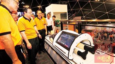 槟州首席部长林冠英参观槟城圆顶科学馆内的其中一项先进的展览品,左为王寿苔及右为槟城圆顶科学馆首席执行员邝云龙。