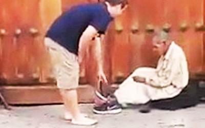 善心男子把自己的一双球鞋脱下来送给露宿者。
