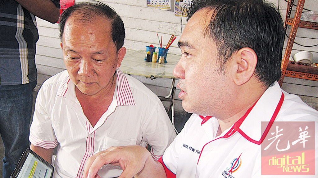 陆兆福(右)向村民讲解选区调动事宜,为村民廖世营上网查证,网站显示国州选区为芙蓉及冷京选区。