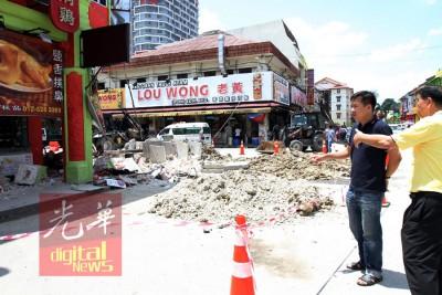 黄文标(左)与当地商家在现场观察坍塌的情况。