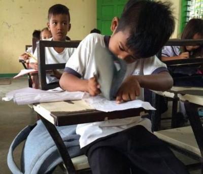 小男孩利用胶拖鞋当擦胶,修改笔记内容。