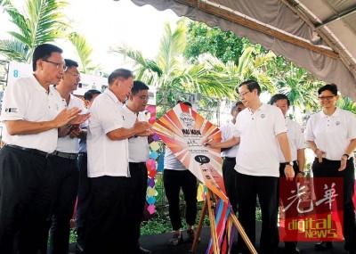 """林冠英(右3)在左起洪永泰、郑来兴、林峰成、黄汉伟、曹观友和洪敏芝陪同下,在风筝上签名,像征入遗庆典""""起飞""""。"""