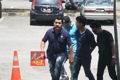 嫌犯(右2)由3名警官押上法庭。
