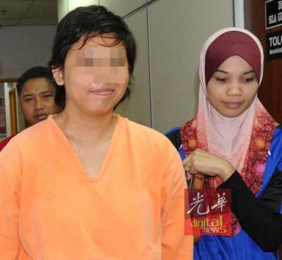 嫌犯由公安部押离法庭时,笑着面对镜头。