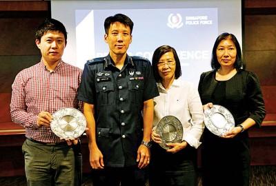 中央警署署长刘国良颁发奖牌,表扬汇款公司职员李述(左1)及汤云英(右2)。