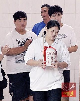 庄莉萍手捧着母亲陈素心的骨灰瓮前往祭拜。