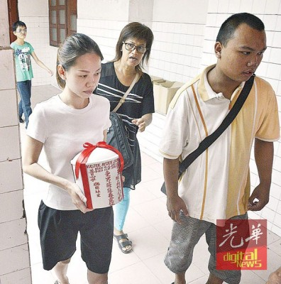 陈妍君神情忧愁的捧着爱儿庄廷森的骨灰瓮。