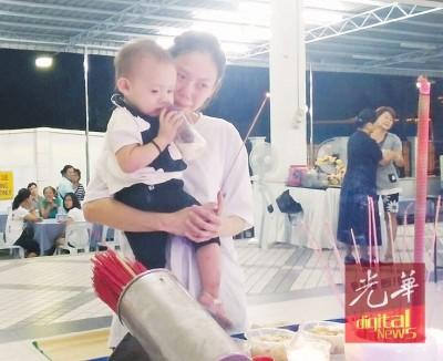 陈妍君抱着一岁女儿,让她向亡父上香。