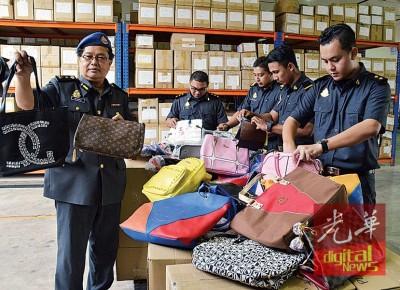 苏海米(左)及贸消部官员查看被充公的名牌包包赝品。