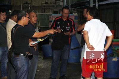 警员向与宰鸡场有业务来往的商人了解状况。