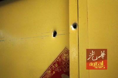 子弹贯穿铁门,留两处弹孔。