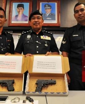 沙菲因(中)展示起获的假枪。