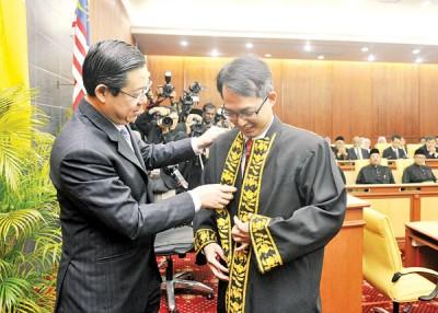 林冠英为刘子健整理议长袍。