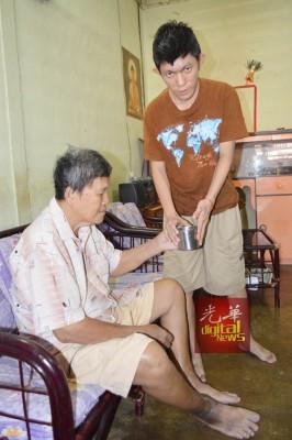 孝顺的陈俊豪(右)虽然智力问题,平时都会倒杯水给父亲陈国海饮用。