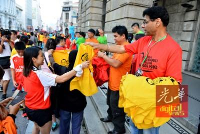 """行动党现场派发印有""""与冠英同在""""的免费T恤予民众,5种颜色不同尺寸供人选择。"""