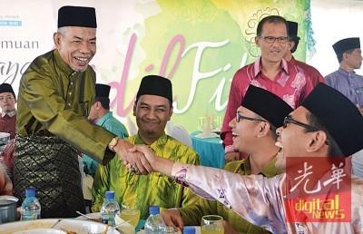 阿兹米丁(左)向出席开斋节开放门户活动的嘉宾握手问候。