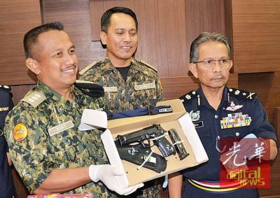 """吉打警方刑事调查主任纳西尔(右)向媒体展示在马泰边境起获的""""巴雷达""""手枪和子弹。"""
