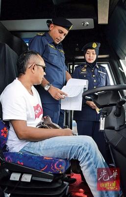 诺鲁哈比(中)检查司机的证件及长途巴士的维修记录。