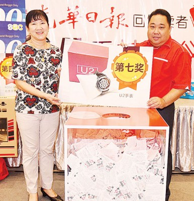 张易雄(右1)于陈华华见证下,抽出第七奖:5卖U2表。