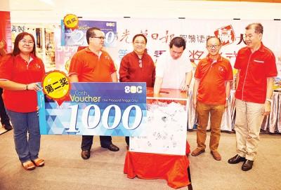 韩帼锠(右3)于林炎葵(左3)、李兴前(右2)、林星作(左2)跟王平松(右1)伴随下,抽出第二奖:总值1000令吉SEC现礼券。