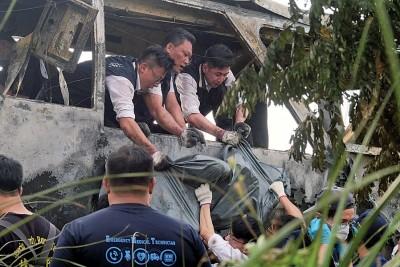 调查人员将乘客遗体逐一移出。(法新社照片)