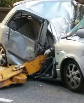 轿车被起重机吊臂压毁。