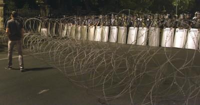 警官在向警局的路口,隔着铁丝网与示威者对峙。(法新社图片)