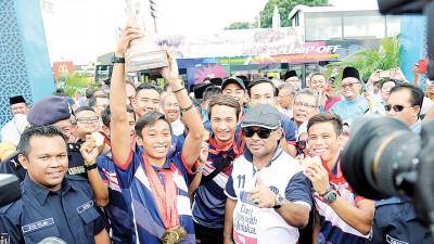 凯鲁(左2)在马六甲州首长拿督斯里依德利斯哈仑(右2)陪同下庆祝会上向到来的公众展示胜利品。