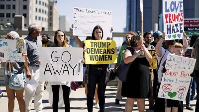 会场外,示威者举牌,抗议特朗普贬低女性。