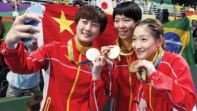 中国乒乓女团金牌功臣丁宁(左起)、李晓霞与刘诗雯赛后在现场兴奋自拍。