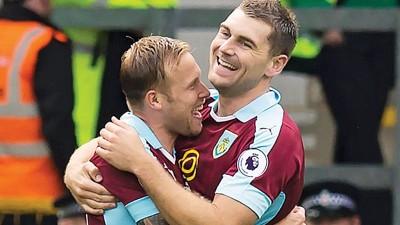 沃克斯(右)首次破门后与队友相拥庆贺。