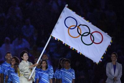 东京都知事小池百合子挥舞奥运五环旗,表示奥运会上东京时。