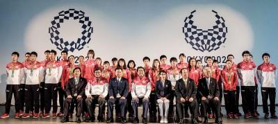安倍晋三(前排中)同勇夺奥运银牌的日本男子400米接力队,与其他健儿官员合影。