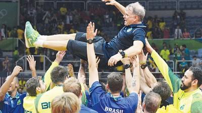 巴西排球队在决赛胜出后球员们兴奋之团结抛起功勋教练博纳多蕾泽德庆祝。