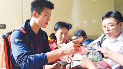 获得里约奥运会羽毛球男子单打冠军的中国选手谌龙(左)在机场为球迷签名。