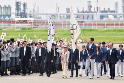 小池百合子(中)手持奥林匹亚会旗步下飞机。