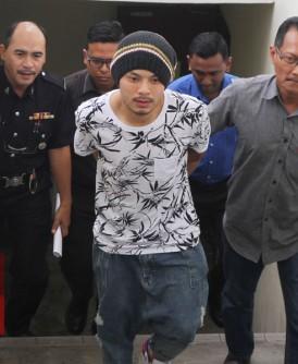 黄明志双手被铐,被警方从槟城法院押往推事庭。