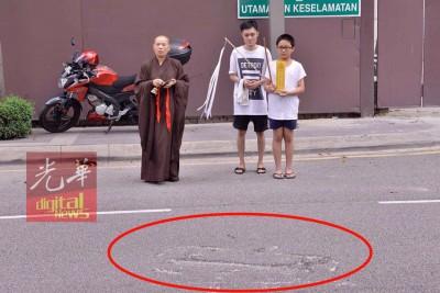 陈群欣的哥哥和弟弟在法师带领下,强忍悲痛重返现场招魂。红圈处为吊臂坠落后所造成的路面痕迹。